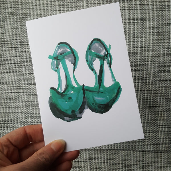 green shoes greeting card being held in front of the camera by a hand.