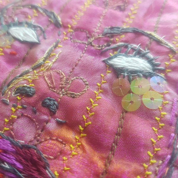 Embroidery close up showing sequins and eyes