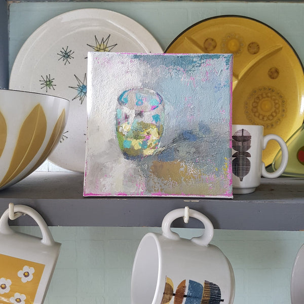 Painting by Julia Laing sitting on a shelf beside midcentury design bowls and plates.