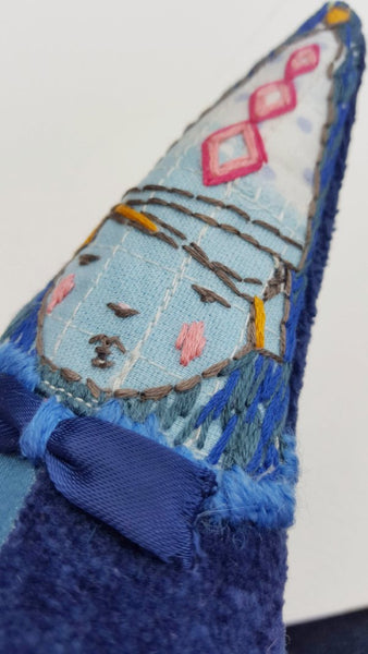 Side view of embroidered face of blue textile art soft sculpture.