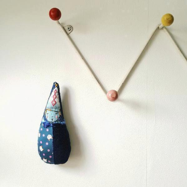 Blue teardrop soft sculpture hanging from coathooks