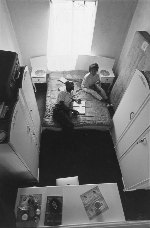 Untitled [Aerial view of couple sitting in bedroom]