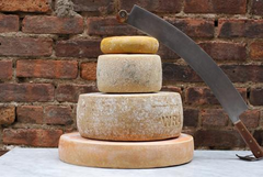 Stacked cheese wheels and cheese knife at Bedford Cheese Shop