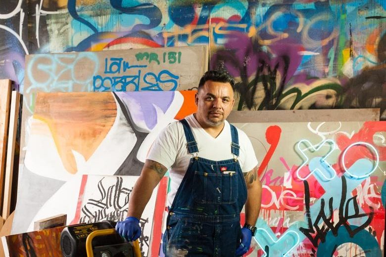 Karlos Marquez Portrait in front of paintings