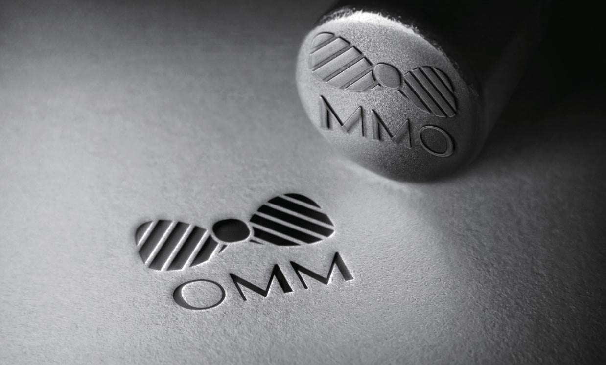 The OMM logo stamped on paper.