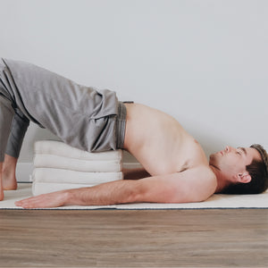 a male yogi is using two stacked white yoga bolsters to support him in bridge pose the man is lying on a white yoga mat
