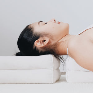 a young woman lying down in savasana pose with two white yoga bolsters supporting her neck and back