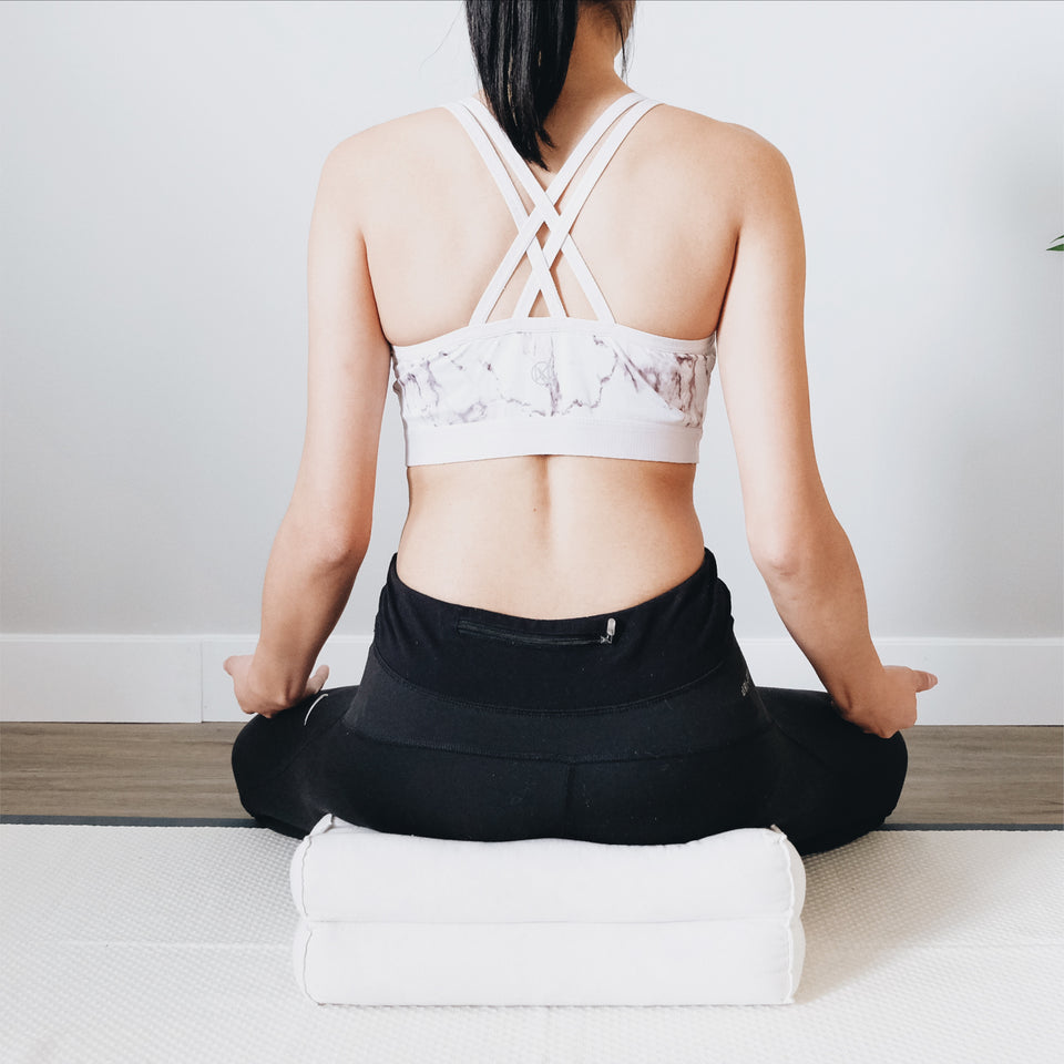 a woman is sitting in a cross legged meditation pose on a meditation cushion