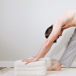 a male yogi is using a set of two yoga blocks to support him in forward fold pose in yoga while standing on a white yoga towel