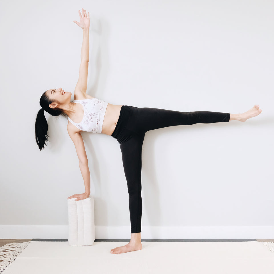 female yogi doing a home yoga workout with a yoga block to support her in half moon pose on a white yoga mat