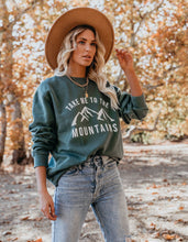 Green take me to the mountains women's sweatshirt. brown wide brim velvet hat, and blue jeans.