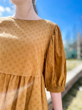 Woman wearing cute mustard yellow baby doll style spring dress with mid length sleeves and full skirt front close up.