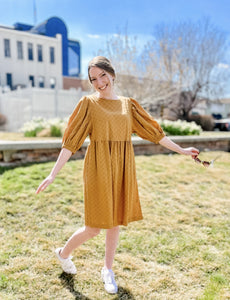 Woman wearing cute mustard yellow baby doll style spring dress with mid length sleeves and full skirt front.