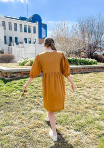 Woman wearing cute mustard yellow baby doll style spring dress with mid length sleeves and full skirt back.
