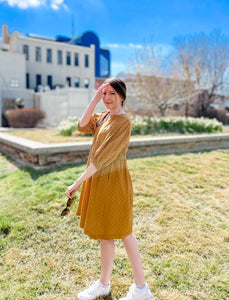 Woman wearing cute mustard yellow baby doll style spring dress with mid length sleeves and full skirt side.