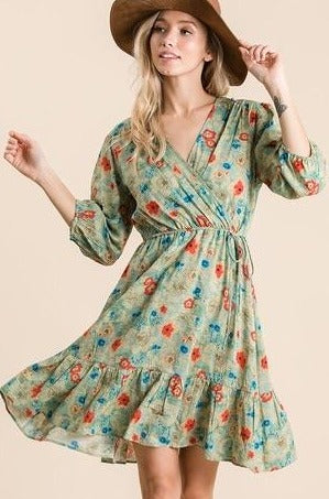 Lightweight green mini dress with all over colorful floral print with adjustable tied waist and v neck front