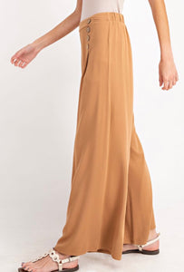 Woman wearing Light brown Carmel colored wide leg dress work trousers with button details on waist side.