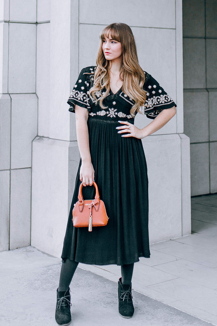 Woman in solid black maxi dress with in bordered bust and flutter sleeves BoHo style