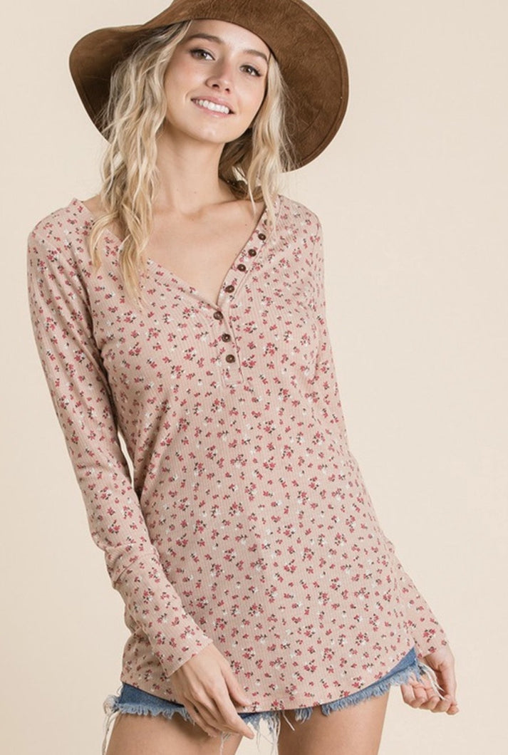 Women wearing plush colored lightweight shirt with pink and white daisy pattern button details along V neck long sleeves front.