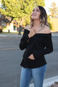 woman in Solid black tuxedo style off the shoulder long sleeve top.