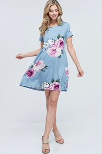 Woman wearing light blue mini soft material dress with purple floral pattern and bow tie back detail front.