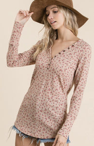 Women wearing plush colored lightweight shirt with pink and white daisy pattern button details along V neck long sleeves side.