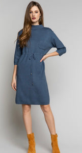 Blue sweater dress with mock neckline, front pocket, and tie front detail.