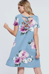 Woman wearing light blue mini soft material dress with purple floral pattern and bow tie back detail back.