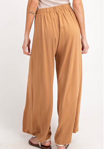 Woman wearing Light brown Carmel colored wide leg dress work trousers with button details on waist back.
