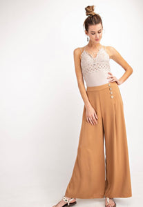 Woman wearing Light brown Carmel colored wide leg dress work trousers with button details on waist front.