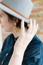 Woman wearing boho wood and gold drop earrings for pierce ears.