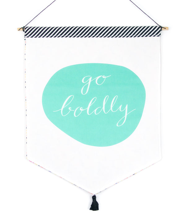 a hanging banner with black and white striped trim on top and a black tassel at the bottom, with the phrase Go Boldly inside of a round teal shape in the center
