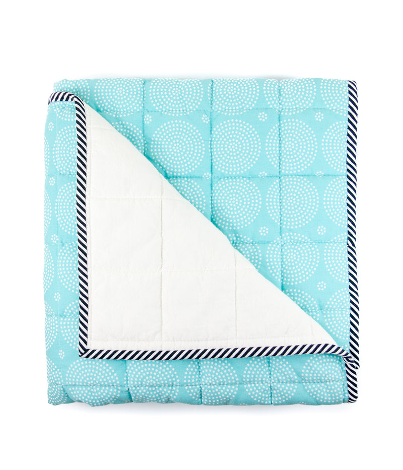 an image of a blue and white blanket folded neatly with one corner flipped down to show the backside