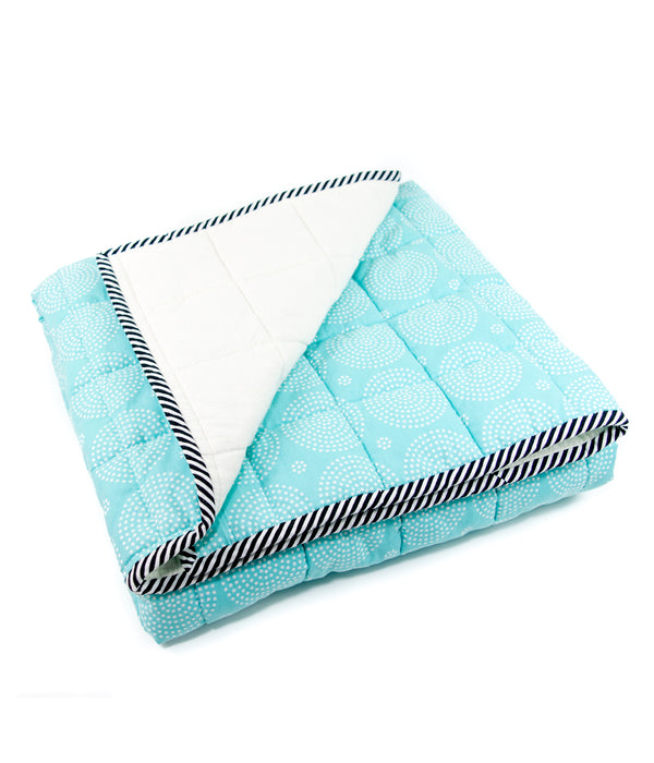 the side view of an image of a blue and white blanket folded neatly with one corner flipped back to show the backside