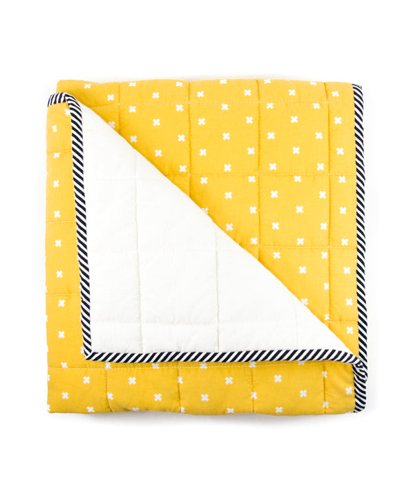an image of a yellow and white blanket folded neatly with one corner flipped down to show the backside