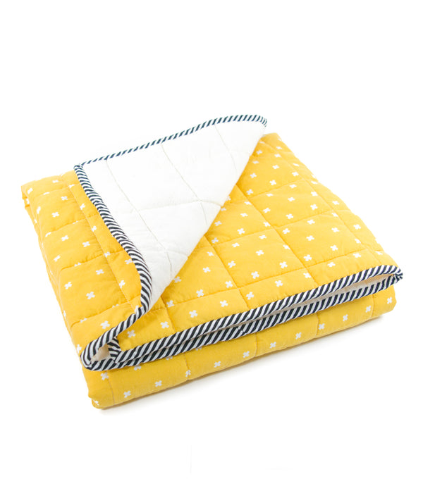 the side view of an image of a yellow and white blanket folded neatly with one corner flipped back to show the backside