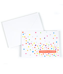 a white envelope and a greeting card, that is printed with the saying Congratulations and has colorful confetti on it