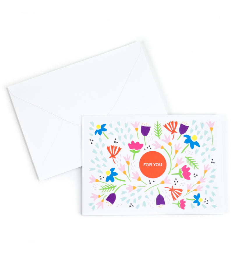 a white envelope and a greeting card, that is printed with the saying For You and has bright floral pattern surrounding it