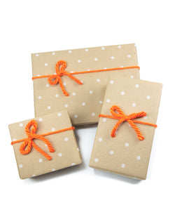three gift boxes wrapped in brown kraft paper, tied with orange bows