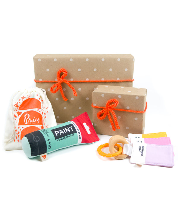 a selection of Prim Society baby products arranged with two gift boxes that are wrapped