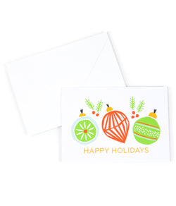 a white envelope and a greeting card, that is printed with the saying Happy Holidays and has green and orange Christmas ornaments on it