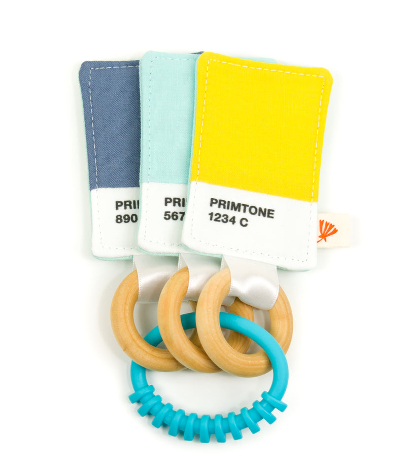 a baby teething toy; three colored swatches attached to wooden rings grouped together by a plastic link