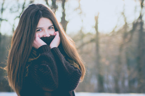 woman covering face in winter