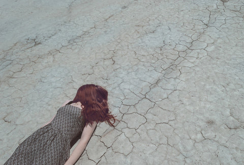 woman lying on dry soil