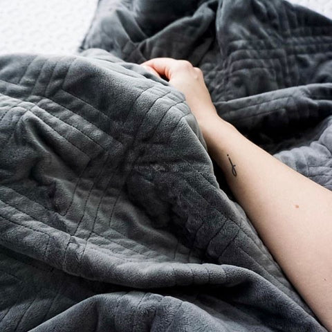 hand resting on a dark grey weighted blanket