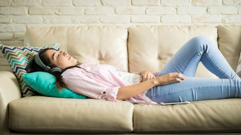 girl laying on a couch with headphones on and listening to music