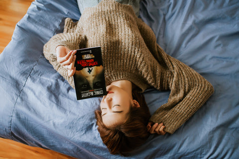 woman lying in bed while holding a book