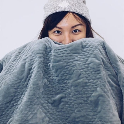 girl covering half of her face with a weighted blanket