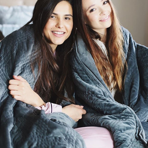two girls wrapped in a Hush weighted blanket smiling at the camera