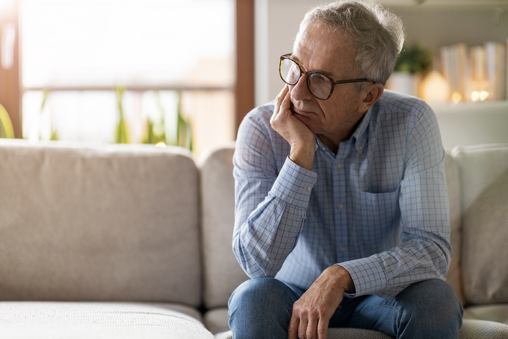 how do you handle stress: Elderly man sitting on a couch while deep in thought